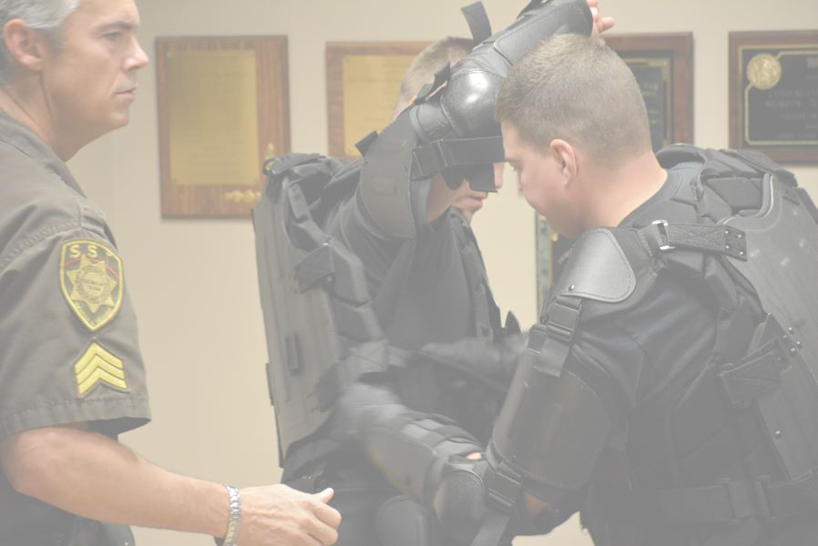 Officer Helping Another Officer Put on Gear