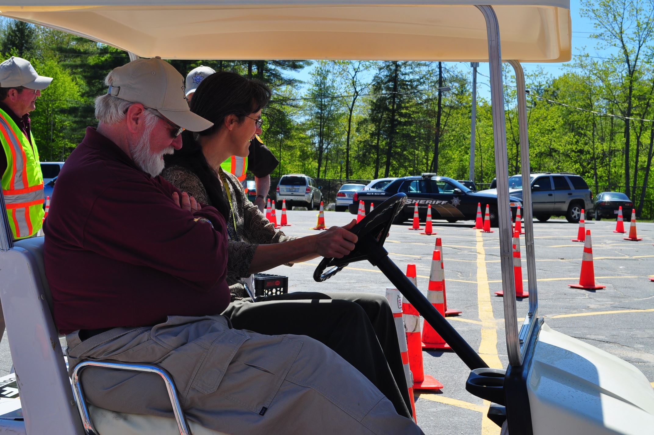 Two People Driving a Golf Cart in a Parking Lot